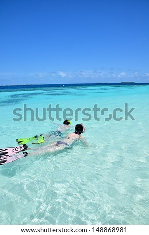Young couple snorkeling in clear tropical turquoise waters  - stock photo