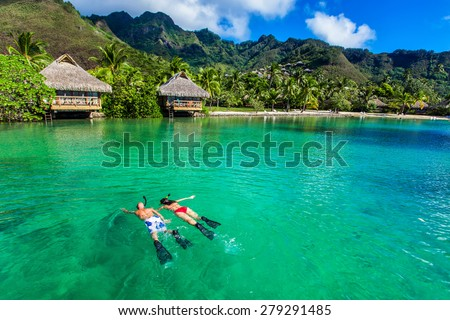 Young couple snorkeling over reef next to resort on a tropical island with over-water villas - stock photo