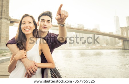 Young couple spending time in New york city. Hugging each other on New york pier and having fun. Good mood and love feelings during urban exploration - stock photo