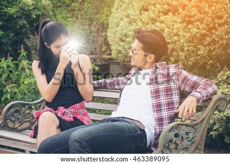Young couple spending time together in the park in summer sunny day. Taking photo of each other.