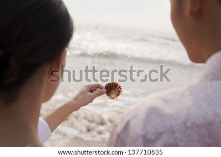 Young couple standing and looking at seashell on the beach, over the shoulder view - stock photo