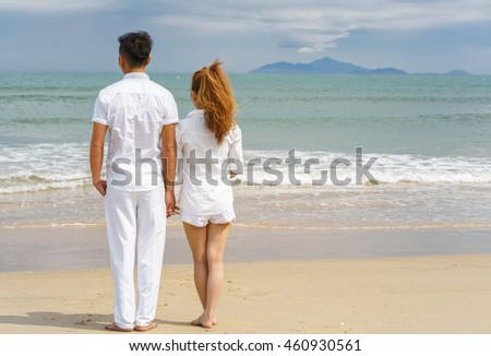Young couple standing and looking at the sea at the China Beach in Danang, in Vietnam