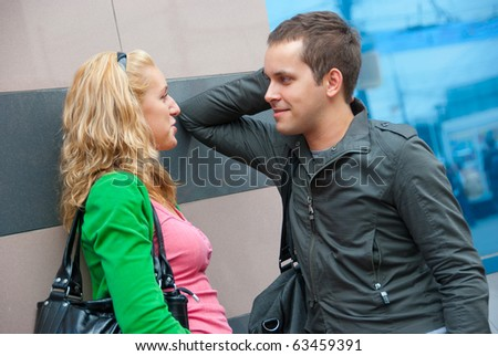 Young couple standing and talking in a city - stock photo