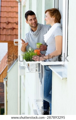 Young couple standing at balcony, having coffee, chatting, smiling. - stock photo