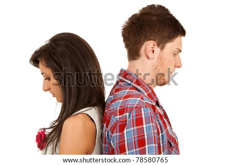 Young couple standing back to back having relationship difficulties on white background - stock photo