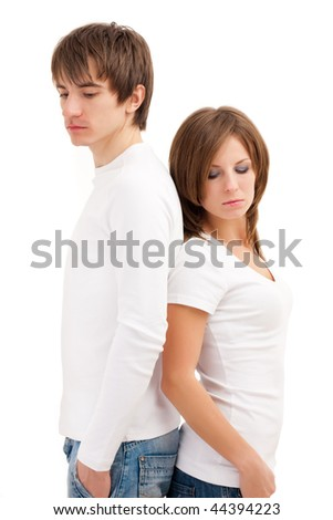 Young couple standing back to back in sadness - stock photo