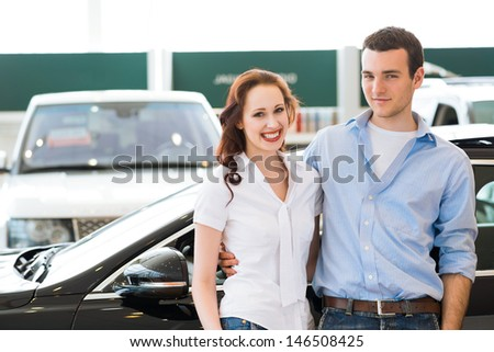 Young couple standing embracing near a car in the showroom - stock photo