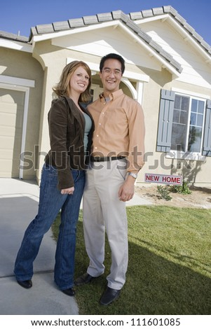 Young couple standing in front of a new house