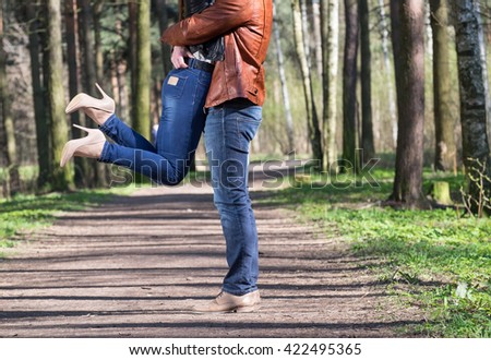 Young couple standing in spring park. Boy lift his girl and she bending her legs - stock photo