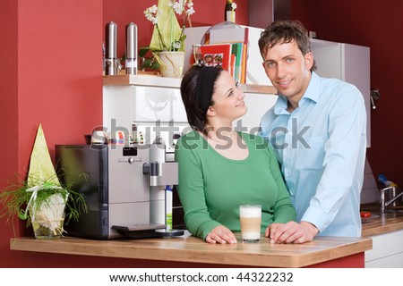Young couple  standing in the kitchen beside a coffee machine - stock photo