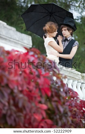 Young couple standing in the rain. - stock photo