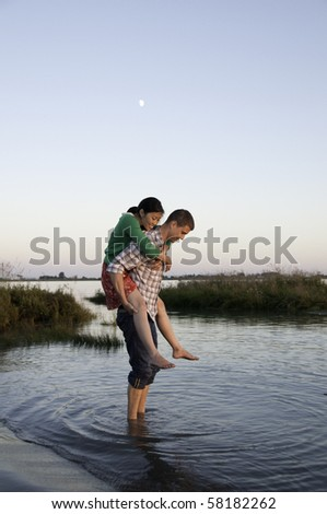 Young couple standing in water . - stock photo