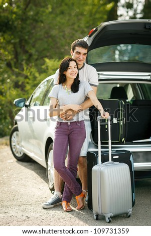 Young couple standing near the opened car boot with suitcases, looking to the camera, outdoors - stock photo