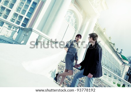 Young couple standing near the orangery in sunlight and holding hands - stock photo