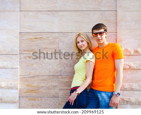 Young couple standing near the wall outdoors  - stock photo