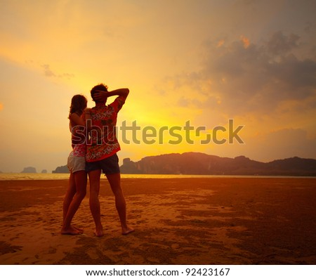 Young couple standing on a beach and looking to a sunset sky - stock photo