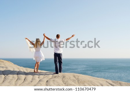 Young couple standing on a rock and raised her hands to the sky - stock photo