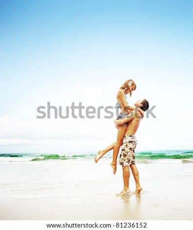 Young couple standing on a sand and enjoying each other