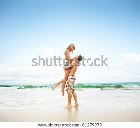 Young couple standing on a sand and enjoying each other - stock photo