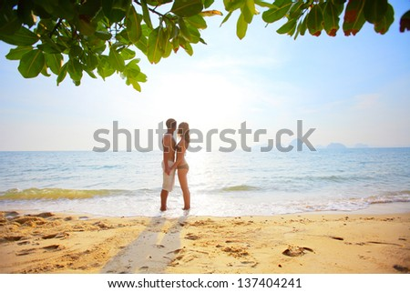 Young couple standing on a sandy beach - stock photo