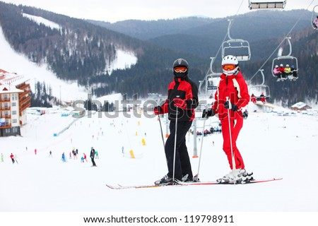 Young couple standing on a ski slope - stock photo