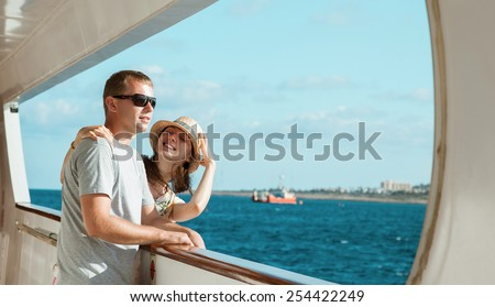 Young couple standing on board the ship - stock photo
