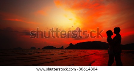 Young couple standing on sand by sea on red dramatic sunset background - stock photo