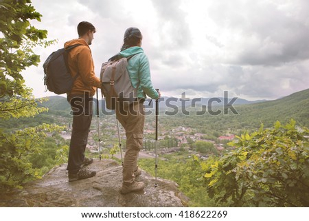 Young couple standing on the edge and staring at the mountains. Toned Image. - stock photo