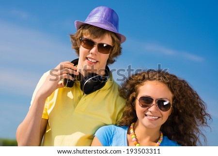 young couple standing on the road, having fun with friends