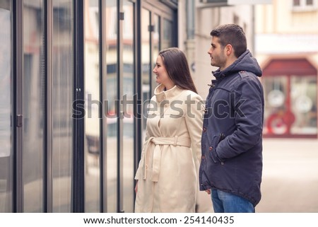 Young couple standing on the street looking at store window