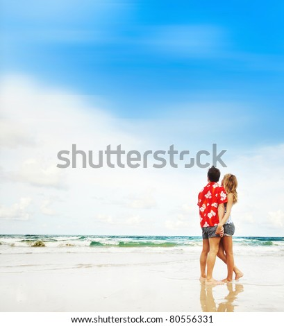 Young couple standing on wet sand by sea and looking to a blue sky - stock photo
