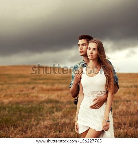 Young couple standing outdoor in the rainy field together. Handsome man with pretty blond woman in love - stock photo