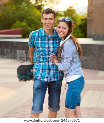Young couple standing outdoors - chatting and having fun - stock photo
