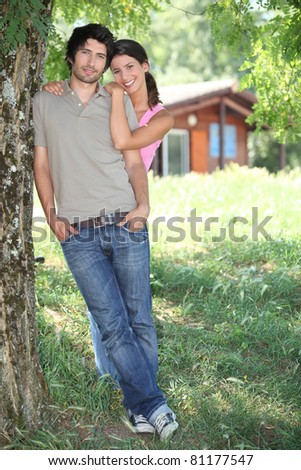 Young couple standing outside a wooden cabin - stock photo