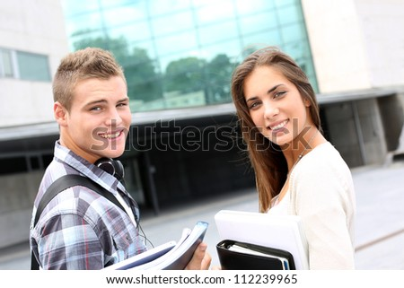 Young couple standing outside university campus - stock photo