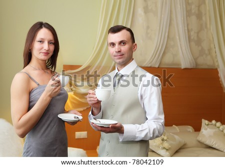 young couple standing together and holding tea cups