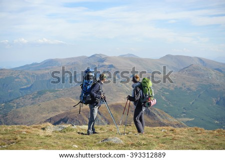 Young couple standing together on the mountain summit enjoying beautiful open view in nature during hiking travel. Hiking gear/equipment. Man and woman using trekking sticks.
