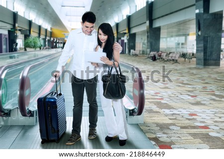 Young couple standing with suitcase in international airport - stock photo