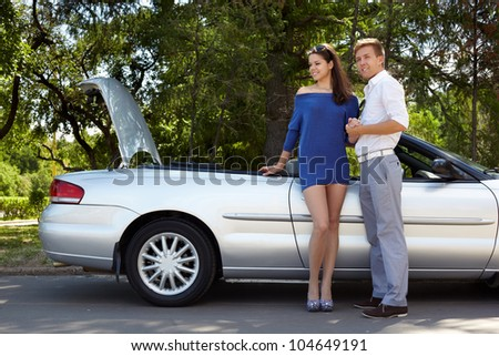 Young couple stands near a cabriolet with opened trunk - stock photo