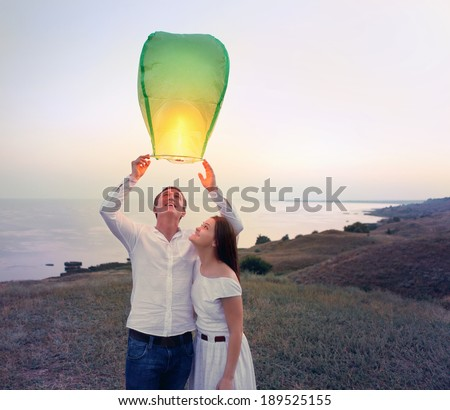 Young couple start a green Chinese sky lantern in the dusk near the sea - stock photo