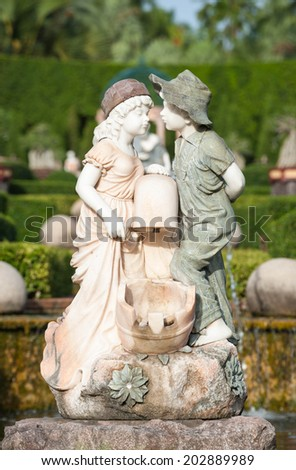Young couple statue in garden - stock photo