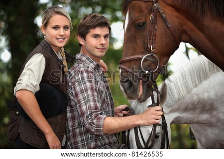 Young couple stood by horses - stock photo