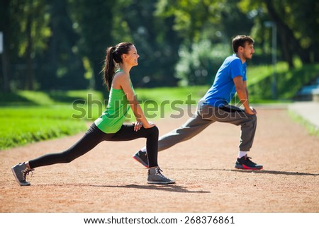 Young couple stretching bodies, warming up for jogging - stock photo