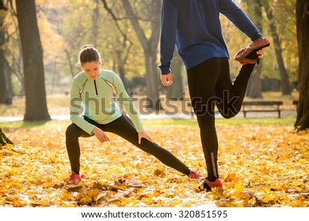Young couple stretching legs before running in autumn nature - stock photo