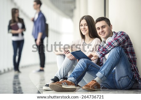 Young couple students sitting in corridor in college. - stock photo