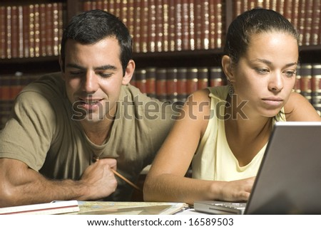 Young couple study together in an office with many books and a computer. Horizontally framed photo. - stock photo