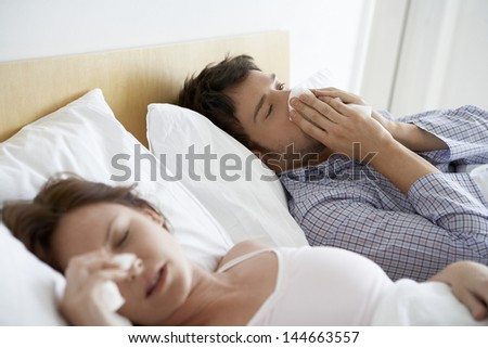 Young couple suffering from colds in bed