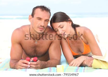 Young couple sunbathing on the beach - stock photo