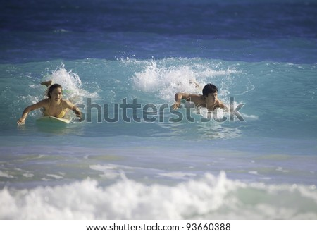 young couple surfing in hawaii - stock photo
