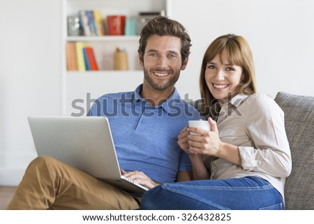 Young couple surfing on internet with laptop. Modern white apartment in background - stock photo